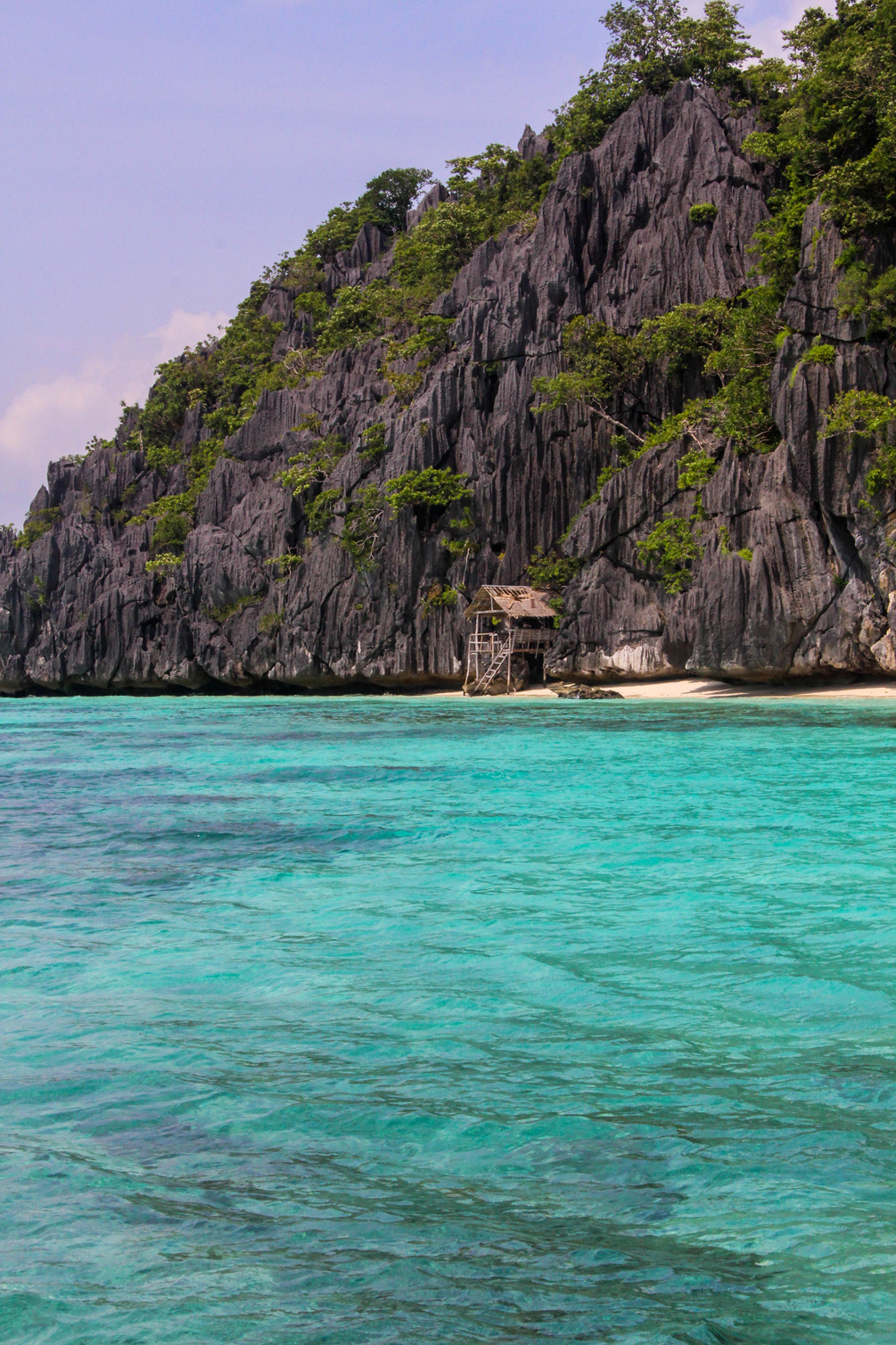 A beautiful scene in Coron, Philippines: a lone shack on the side of a limestone formation. | cat-elle.com